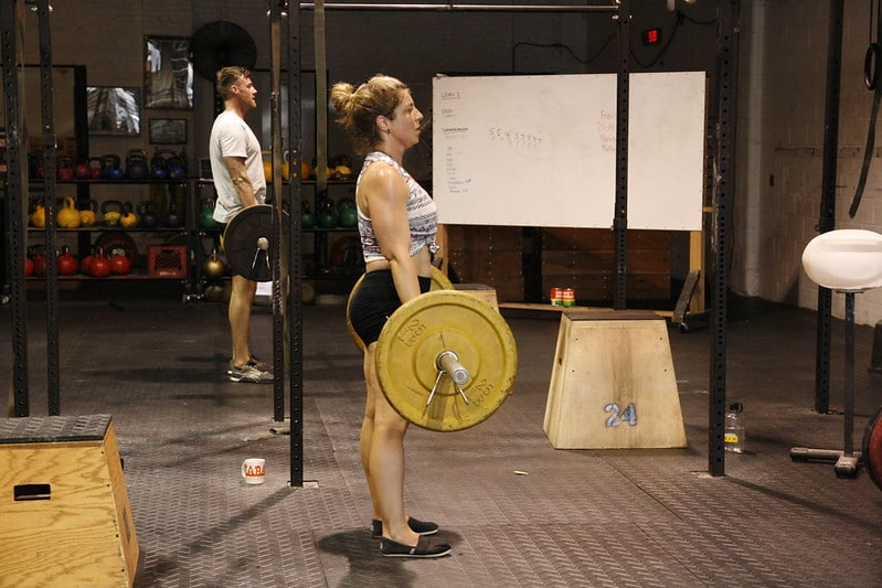 A Woman and a Man in the Gym Performing Deadlifts
