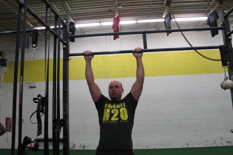 A Man Hanging From a Bar Performing Pull Ups