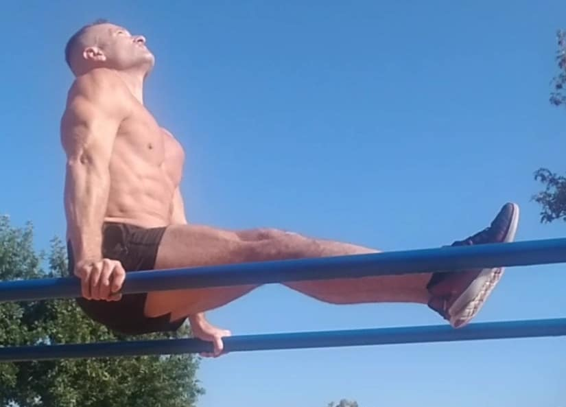 A Man Performing Core Exercises on Parallel Bars