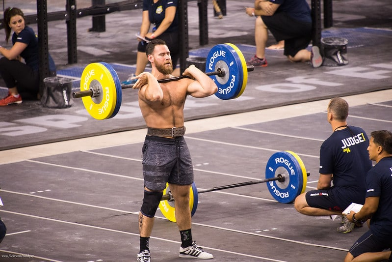 A Man Performing Front Squats While Others Look On