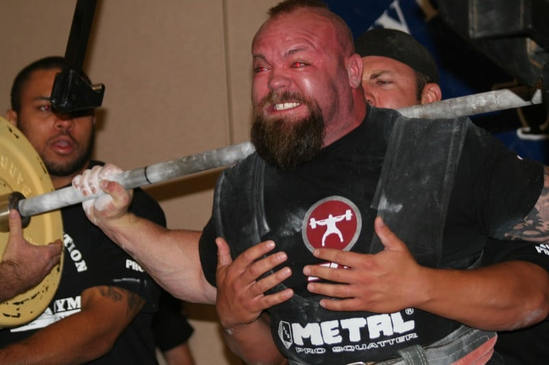 A Man Struggling to Perform a Heavy Squat While Surrounded By Spotters