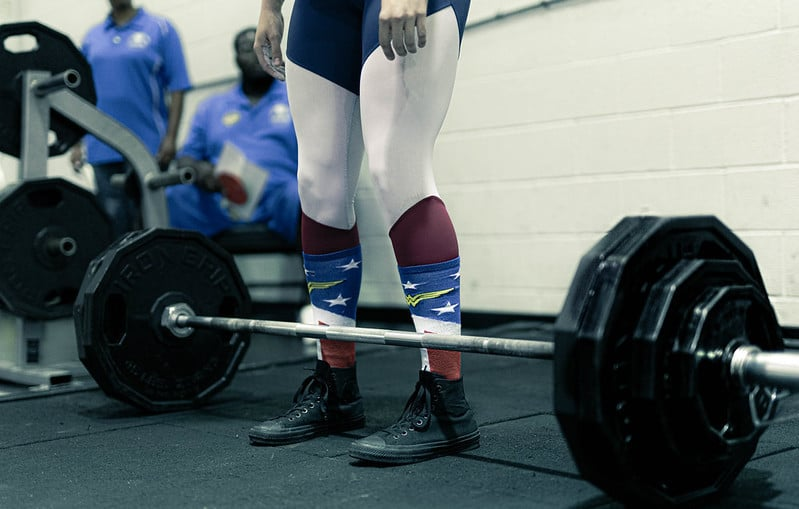 A Person Getting Ready to Deadlift a Heavy Barbell