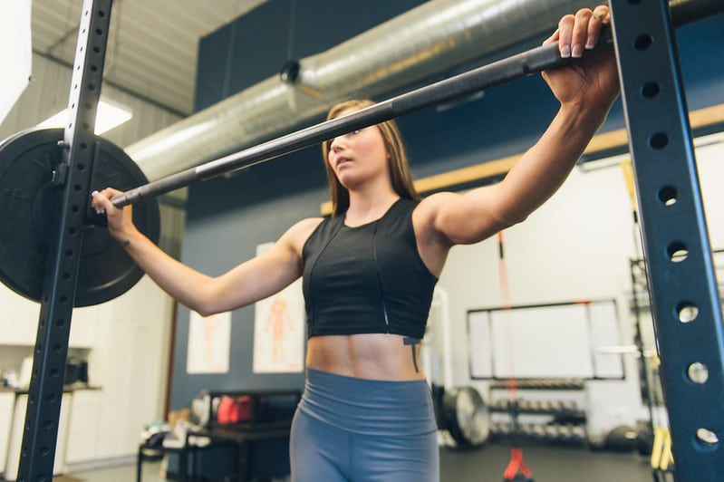 A Woman Standing at the Squat Rack Preparing to Squat