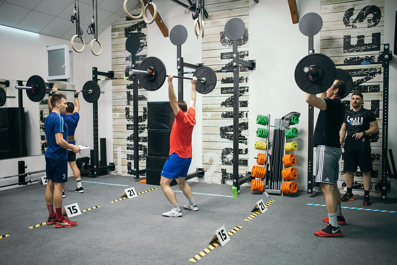 People Training in the Gym Being Instructed How to Shoulder Press