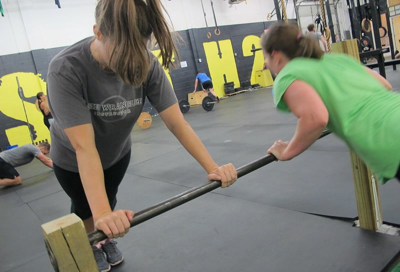 Two Women Doing Incline Push Ups Against a Bar