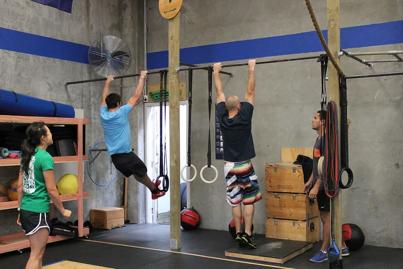 Two Men Performing Pull Ups While Two Other People Look On