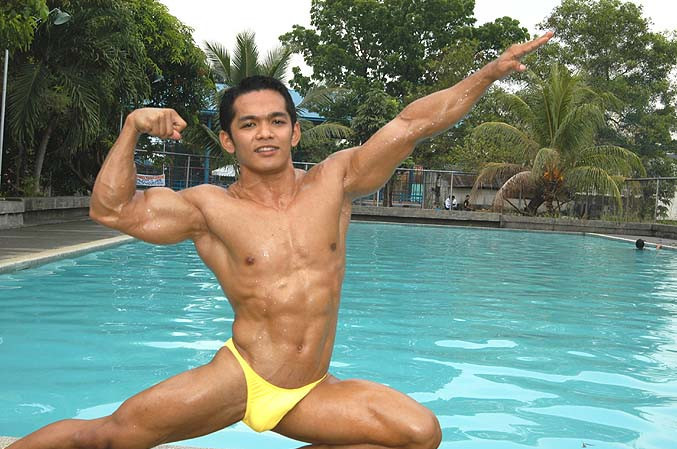 A Bodybuilder Striking a Pose By a Swimming Pool