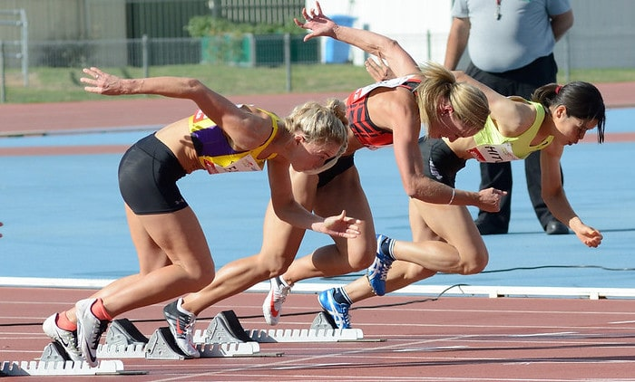 A Group of Women Sprinters Exploding Out of the Starting Blocks