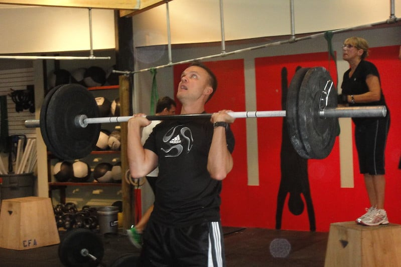 A Man Holding a Weighted Barbell in the Bottom Position of the Overhead Press With Vertical Forearms