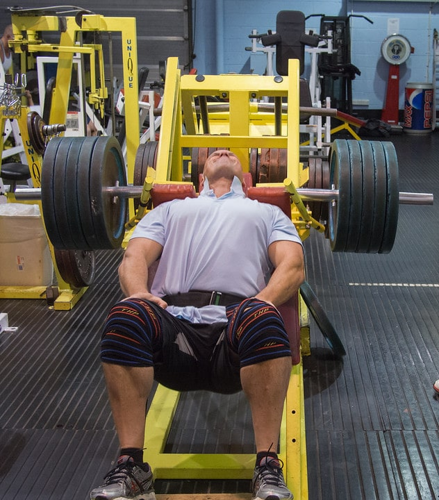 A Man Preparing to Perform the Hack Squat in the Gym