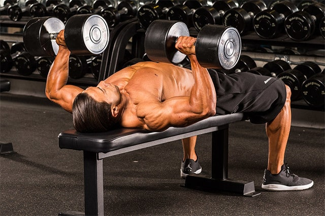 A Muscular Man Performing Dumbbell Chest Press in the Gym