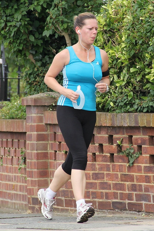 A Woman Jogging While Holding a Water Bottle