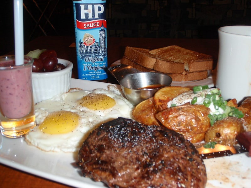 A Table of Food and Condiments Including Steak, Eggs, and Potatoes